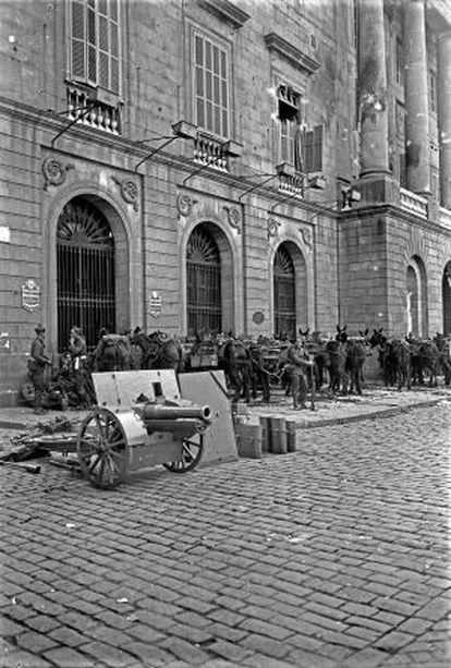 Soldats davant l'edifici de l'Ajuntament de Barcelona, on es poden veure els impactes de l'artilleria durant el Sis d'Octubre.