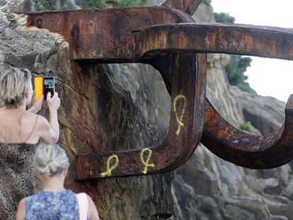 Varios lazos amarillos en una de las piezas metálicas del Peine del Viento de Eduardo Chillida. En vídeo, pintan lazos amarillos en el 'Peine del Viento' de Chillida.