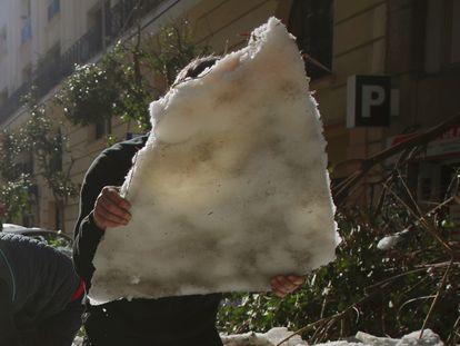 Vecinos retiran con palas el hielo de la calzada en Madrid, tras la borrasca Filomena.