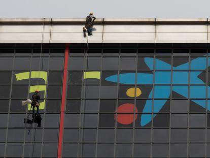 Varios operarios quitan el logotipo de Bankia para incorporar, sobre las ventanas más altas del edificio, la imagen de CaixaBank.