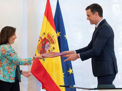 La ministra de Defensa, Margarita Robles, entrega la carpeta con la directiva nacional al presidente del Gobierno, Pedro Sánchez.