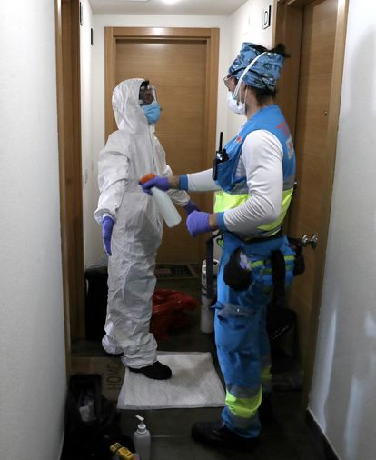 Andrés desinfecta a la enfermera Vanesa Jiménez tras haber estado en la casa de un enfermo de coronavirus, en Alcorcón, Madrid.