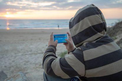 """Un menor juega con su móvil a la aplicación  """"Narcos del Estrecho"""" en una de las playa de Cádiz."""