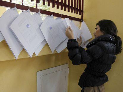 Una ciudadana consultan en las listas de un colegio electoral de Madrid.