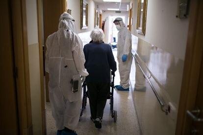 Voluntarios de la ONG Proactiva Open Arms ayudan durante el traslado de ancianos a una residencia sin casos de coronavirus, el pasado 18 de abril en Barcelona.