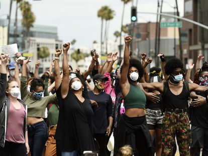 Manfiestantes del movimiento Black Lives Matter alzan el puño en Beverly Hills, California.