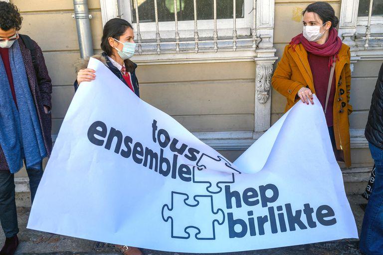 """Dos mujeres sujetan una pancarta en la que se lee """"Todos juntos"""" en francés y en turco durante una protesta de los profesores de la Universidad Galatasaray contras las nuevas restricciones al profesorado extranjero, este martes en Estambul."""