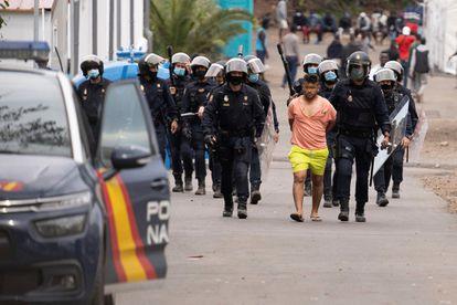 Policías antidisturbios trasladan a un detenido del campamento humanitario de Las Raíces tras los altercados ocurridos en el campamento de La Laguna (Tenerife).