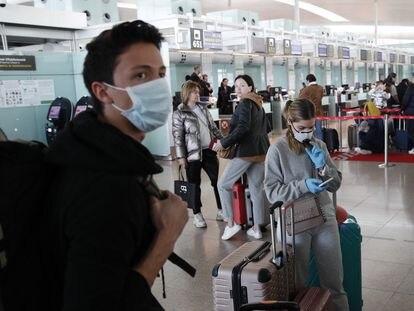 Varios pasajeros esperan para facturar en el aeropuerto de El Prat-Barcelona.