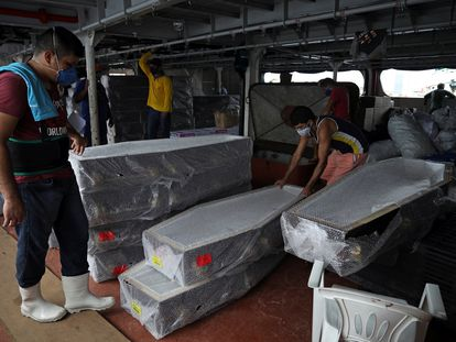 Varios trabajadores desembarcan ataudes llegados este viernes en barco a Manaos desde Santa Catarina (Brasil).