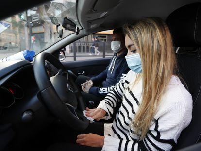 Una alumna de autoescuela junto a su profesor desinfecta el volante del coche para reiniciar las clases.