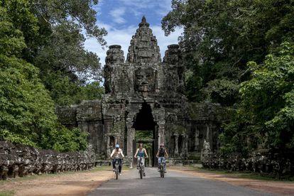 Un grupo de turistas recorre el enorme complejo de Angkor en bicicleta.