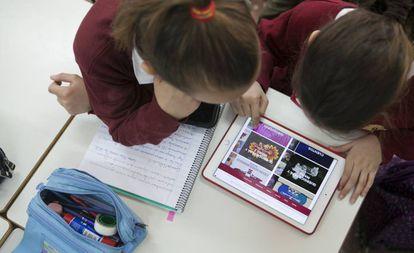 Dos niñas trabajan en clase con una tableta.