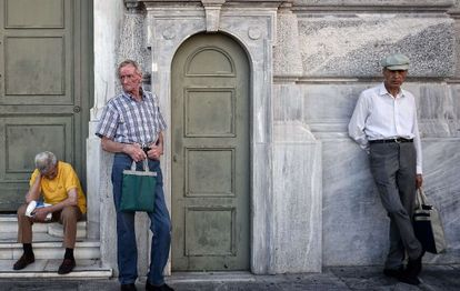 Tres pensionistas aguardan fuera de la sede del Banco Nacional de Grecia, el 9 de julio.