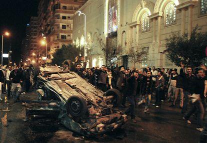 Fieles cristianos protestan junto a uno de los coches destrozados en el atentado frente a una iglesia de Alejandría.