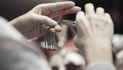 Una mujer elabora una pieza de bisutería.
