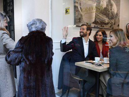 El candidato del PP a las generales, Pablo Casado, sentado junto a la presidenta de la Comunidad de Madrid, Isabel Díaz Ayuso, y su esposa, Isabel Torres, saluda a dos mujeres desde la cafetería donde han desayunado tras votar.