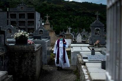 Un sacerdote atraviesa un camposanto durante un entierro en la crisis sanitaria por la Covid-19.