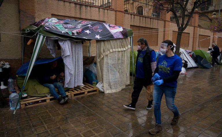 Varios voluntarios reparten comida a personas sin hogar, el pasado jueves en Valencia.