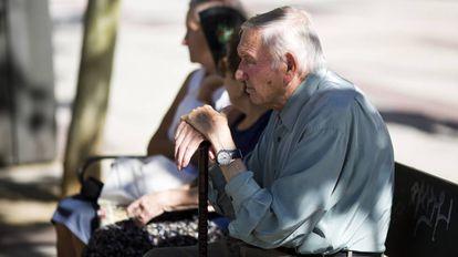 Un hombre mayor, junto a otras ancianas, en un banco en la calle Alcalá (Madrid).