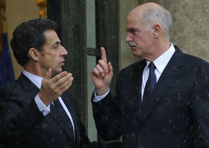 El presidente de Francia, Nicolas Sarkozy, junto al primer ministro griego, George Papandreu, bajo la lluvia en París.