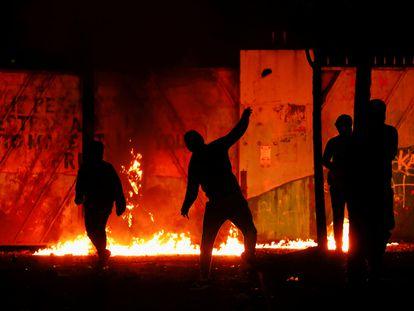 """Manifestantes en la puerta del """"muro de la paz"""" en Lanark Way mientras continúan las protestas en Belfast, Irlanda del Norte."""