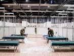 """This handout picture made available by Madrid's regional government, Comunidad de Madrid, on March 26, 2020 shows workers and soldiers working in a temporary hospital set-up for coronavirus infected patients at the pavilion 9 of the Ifema convention and exhibition center in Madrid. - The field hospital currently has 1,500 beds and it could be expanded to take in up to 5,500 people -- which would make it the biggest such facility in Europe. (Photo by Handout / COMUNIDAD DE MADRID / AFP) / RESTRICTED TO EDITORIAL USE - MANDATORY CREDIT """"AFP PHOTO /COMINUDAD DE MADRID """" - NO MARKETING - NO ADVERTISING CAMPAIGNS - DISTRIBUTED AS A SERVICE TO CLIENTS"""