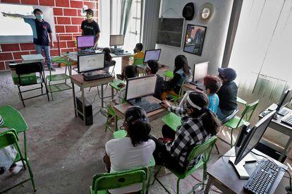 Una maestra de la asociación civil Utopía imparte una lección de informática a niños de la colonia Escalerillas.