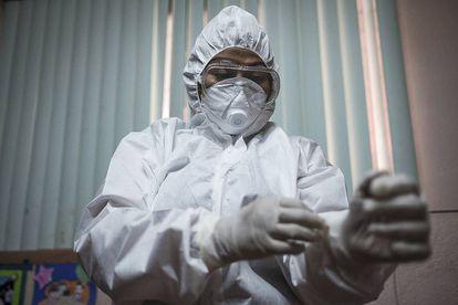 La médico Karen Ojeda se prueba un traje de protección que logró conseguir en el mercado negro, debido a la escasez de este tipo de equipos en Nicaragua.