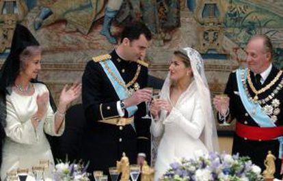 El príncipe Felipe brinda con su esposa, Letizia Ortiz, el día de su boda en presencia de los Reyes.