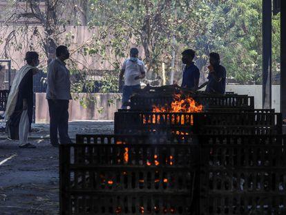Unos familiares de fallecidos a causa de la covid-19, delante de las piras funerarias en la India, el 11 de mayo de 2021 en Ahmedabad.