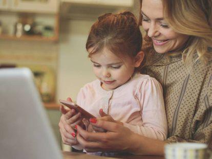 Una niña usa su 'smartphone' junto a su madre.