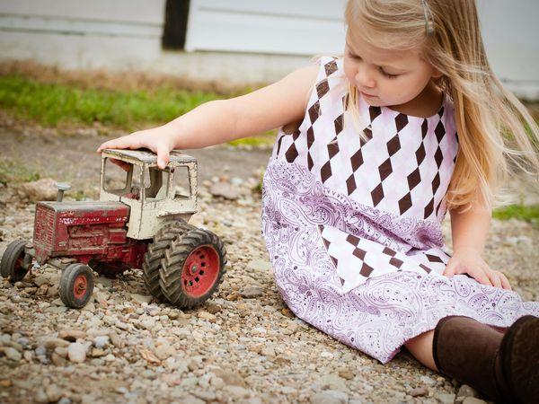 Una niña juega con un tractor viejo.