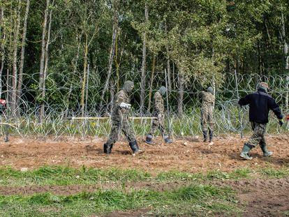 Soldados polacos construyen una valla de alambre de púas a lo largo de la frontera con Bielorrusia, cerca de la aldea de Minkowce, el pasado mes de septiembre.