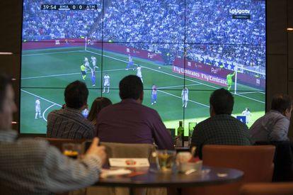 Varios clientes ven un partido de fútbol en un bar.