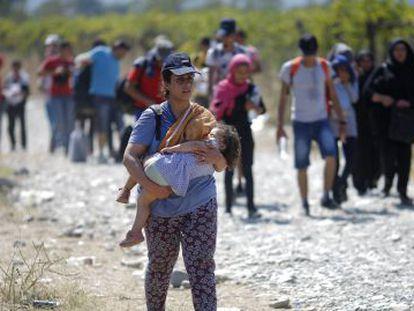 Un grupo de refugiados cruzan la frontera entre Grecia y Macedonia.-