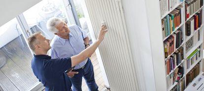 Un operario instala un repartidor de costes en un radiador, un dispositivo de ahorro obligatorio antes de 2017 en calefacciones centralizadas.