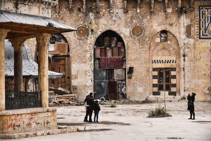 El alepino Hamid Kenefati se fotografía junto a su familia en la Mezquita Omeya de Alepo tras el fin de los combates