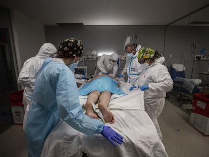 Varios sanitarios trabajan con un paciente infectado por coronavirus en estado muy grave, en una de las salas de UCI del Hospital Isabel Zendal de Madrid.