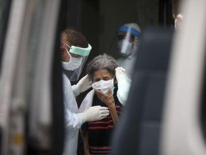 Enfermeros evacúan este miércoles a una anciana de un geriátrico de Buenos Aires donde se ha registrado un brote de covid-19