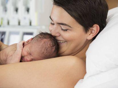 Una madre coge su recién nacido en brazos.