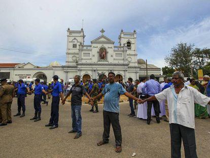 Soldados y ciudadanos srilanqueses hacen un cordón humano frente a la iglesia de San Antonio, en Colombo.