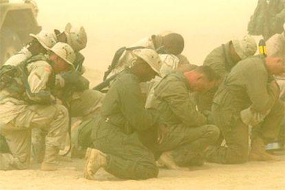 Soldados estadounidenses desplegados en la frontera entre Kuwait e Irak rezan en medio de una tormenta de arena.