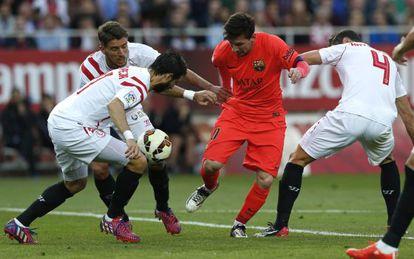 Messi trata de controlar el balón rodeado de jugadores del Sevilla.