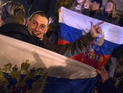 Manifestantes prorrusos en Donetsk celebran el triunfo de la anexión y hacen desaparecer los símbolos ucranios.