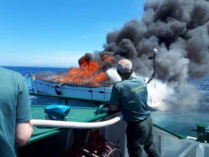 Dos agentes se aproximan al velero sueco en llamas.