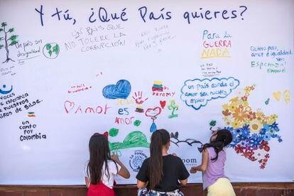 Niños de un colegio del barrio Siloé (Cali) escriben consignas en un muro.