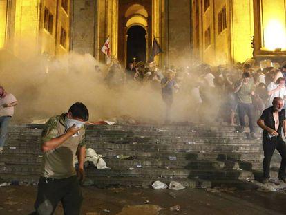 Manifestantes se protegen de una carga de gases lacrimógenos, este viernes en Tblisi.