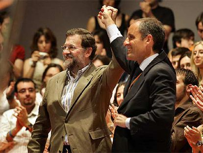 Mariano Rajoy y Francisco Camps levantan sus manos entre los aplausos de los militantes del PP.