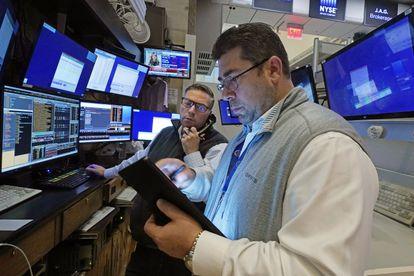 Varios corredores de bolsa trabajan en Wall Street, este lunes.